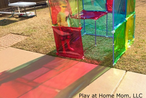 A photo of a child playing in a colourful transparent structure