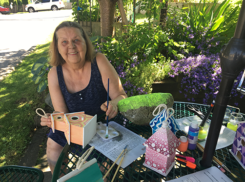 A senior from Beulah Gardens is painting using the Art Kit